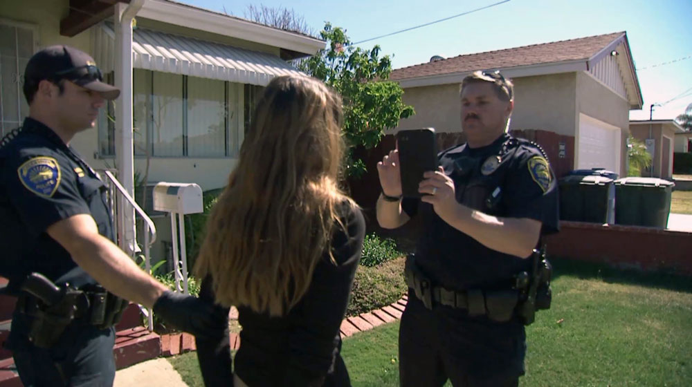 Officer Rob Halverson of the Chula Vista police verifies the identity of a woman just arrest for possession of narcotics with facial recognition software.