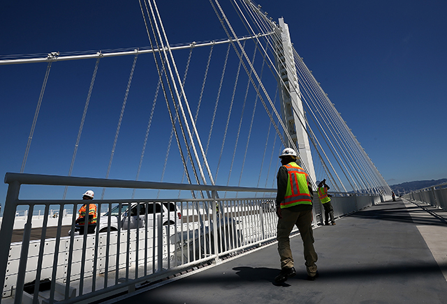 A worker walks on the bike path next to the new Bay Bridge Self-Anchored Suspension tower (Justin Sullivan/Getty Images).