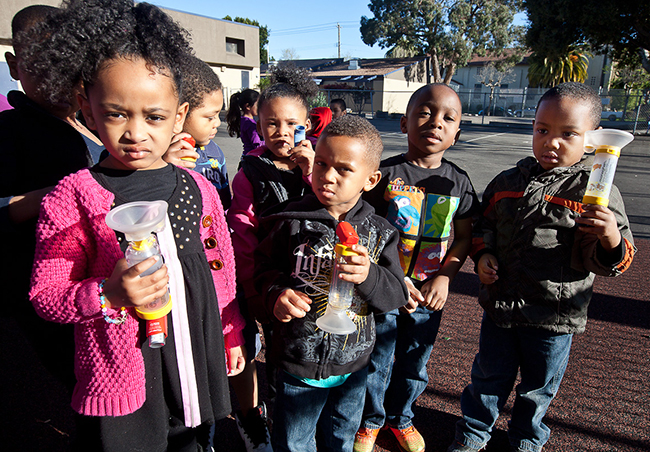 In Jahvonn Mair's preschool class of 22 students, 7 have been diagnosed with asthma and use an inhaler. Here they display their inhalers. From left to right, Akirah Armstrong, (behind) Adrian Kemp, RiJai Malone, Omarr Daniel (front), Jahvonn Mair and Sarquan Holland. (Deborah Svoboda/KQED)