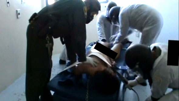 A still image from a video showing California prison guards dousing mentally ill inmates repeatedly with pepper spray.