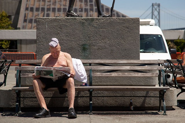 A man suns himself while reading the newspaper next to the Ferry Building (Mark Andrew Boyer/KQED)