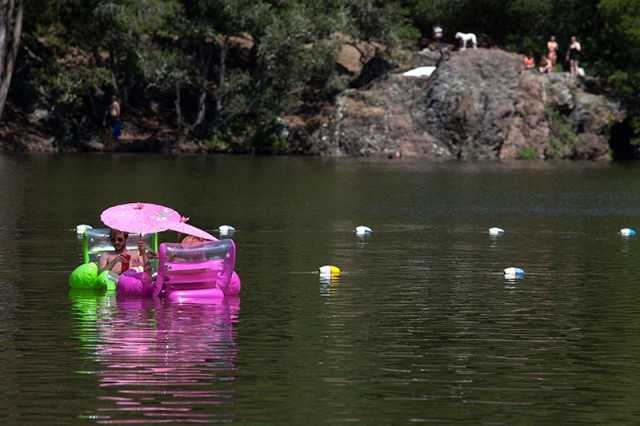 A couple floats on inflatable chairs in Lake Anza (Mark Andrew Boyer/KQED)
