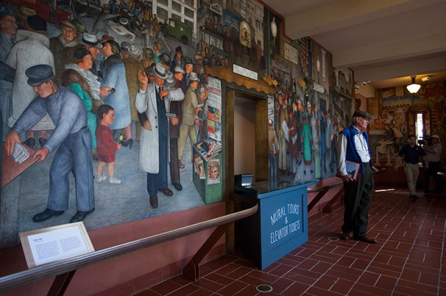 Michael Gorden, a docent for San Francisco City Guides, stands in front of one of Coit Tower's murals (Mark Andrew Boyer / KQED)