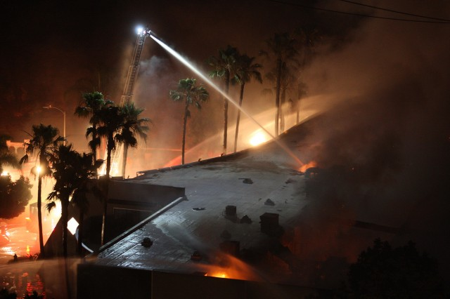 Firefighters spray water on burning building in the San Diego County town of Carlsbad. (David McNew/Getty Images)