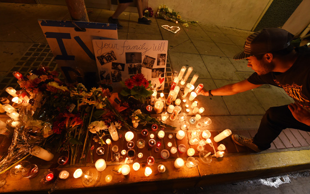 A student lights a candle at a makeshift memorial outside the IV Deli Mart where one of the victims of a killing spree was shot and killed near the University of California, Santa Barbara campus during a candlelight vigil for those affected by the tragedy in Isla Vista on May 24, 2014 in Santa Barbara, California. Elliot Rodger, the British-born son of a Hollywood film-maker stabbed three men to death in his apartment before killing three more people in a shooting spree in Santa Barbara, California, police said. AFP PHOTO/ROBYN BECK (Photo credit should read ROBYN BECK/AFP/Getty Images)