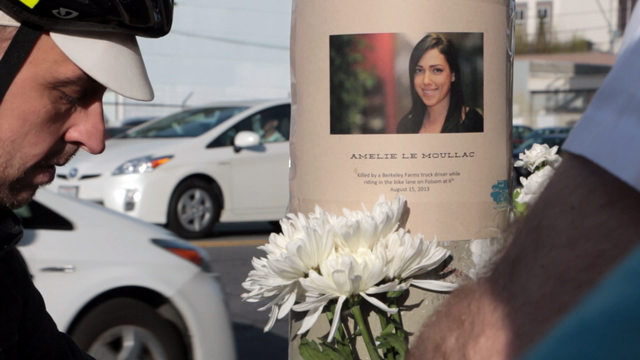 Cyclists post a memorial poster of Amelie Le Moullac during the 2014 Ride of Silence. (Jeremy Raff/KQED)