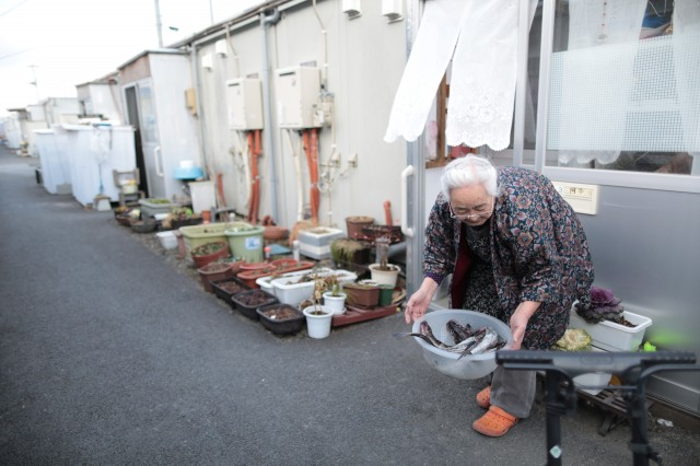 An elderly woman holds a container filled with fish given by her neighbor outside her temporary house. (Yuriko Nakao/Getty Images)