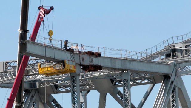 A worker cuts through the a section of the cantilever truss section of the old Bay Bridge. (Adam Grossberg/KQED)