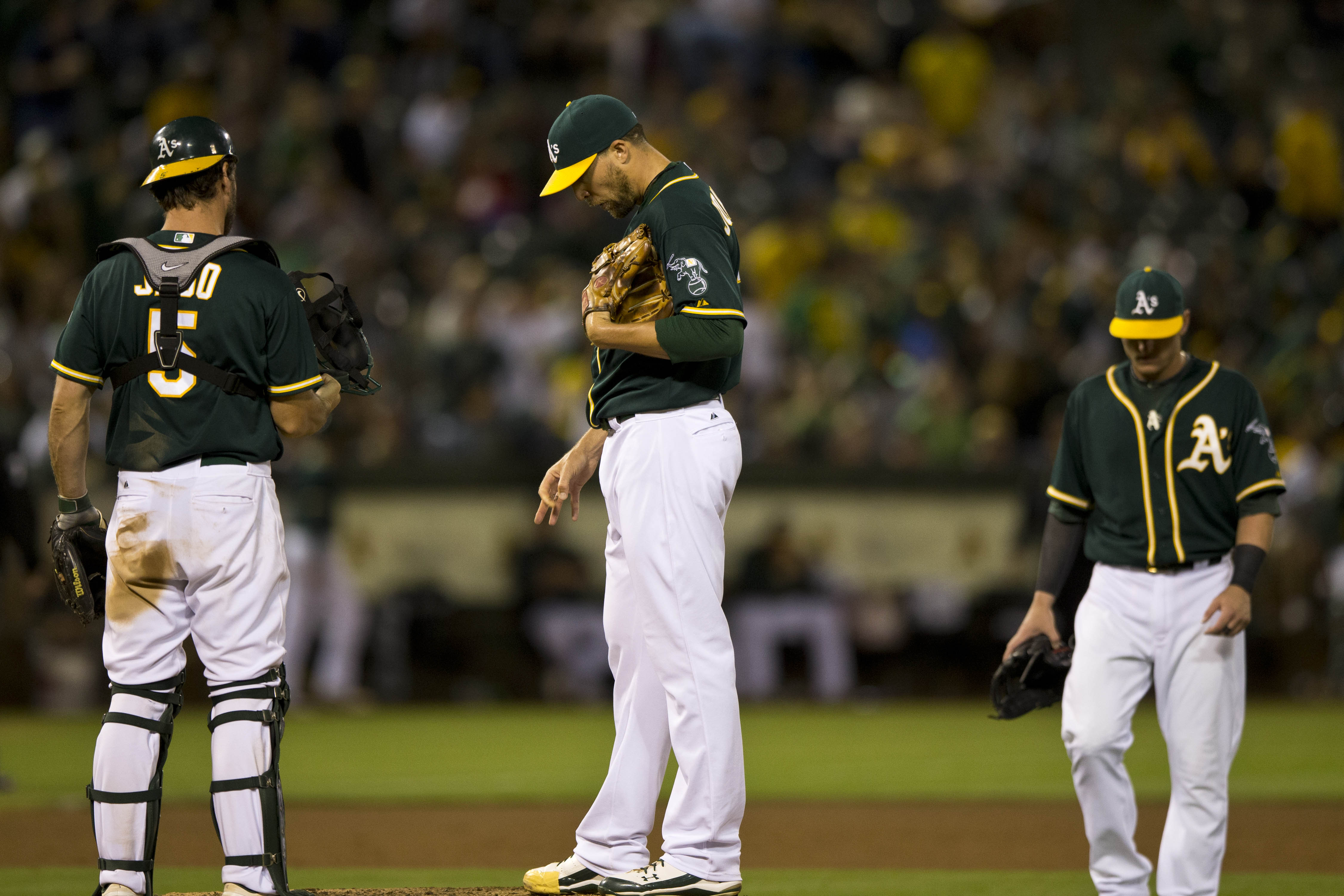 The Oakland A's Jim Johnson, center, on the  mound Wednesday night during the latest in a string of disastrous outings. (Jason O. Watson/Getty Images)