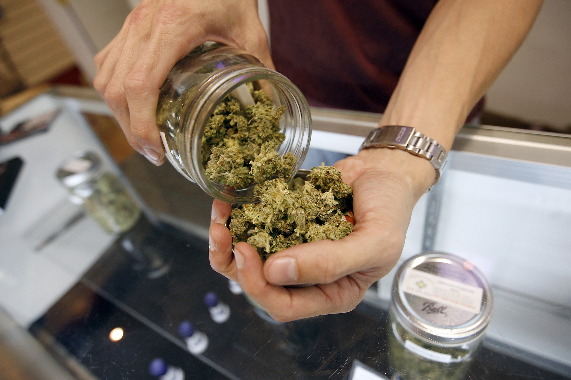 A budtender pours marijuana from a jar at Perennial Holistic Wellness Center medical marijuana dispensary in Los Angeles, California. ( David McNew/Getty Images)