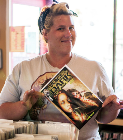 "Villainous Lair manager Sara Swieca holds up an issue of Larime Taylor's ""A Voice in the Dark,"" a graphic series she loves. (Courtesy Mark Walsh)"