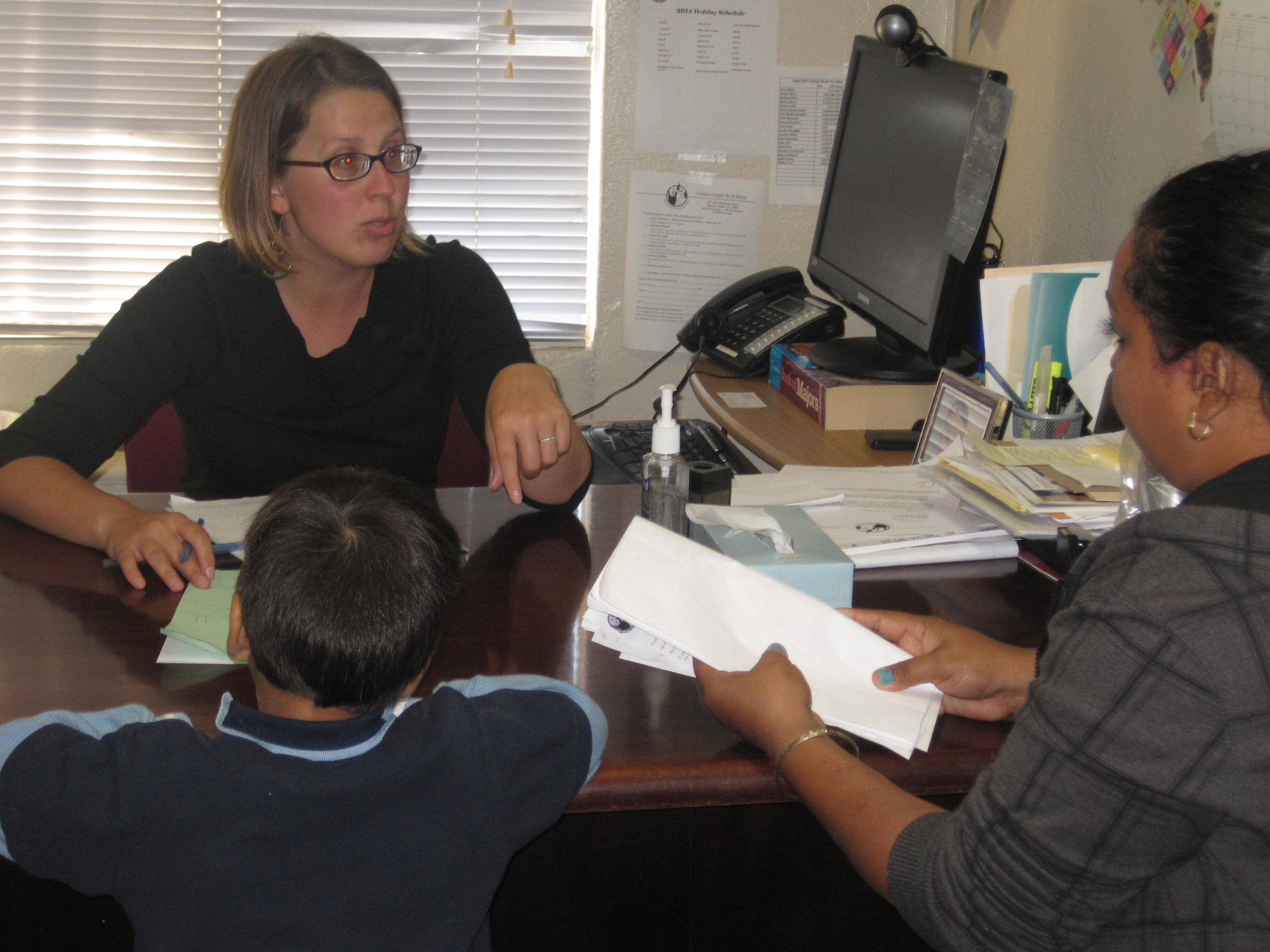 Immigration attorney Eleni Wolfe-Roubatis meets with a tiny client and his mom at Centro Legal de la Raza. (KQED/Zaidee Stavely )