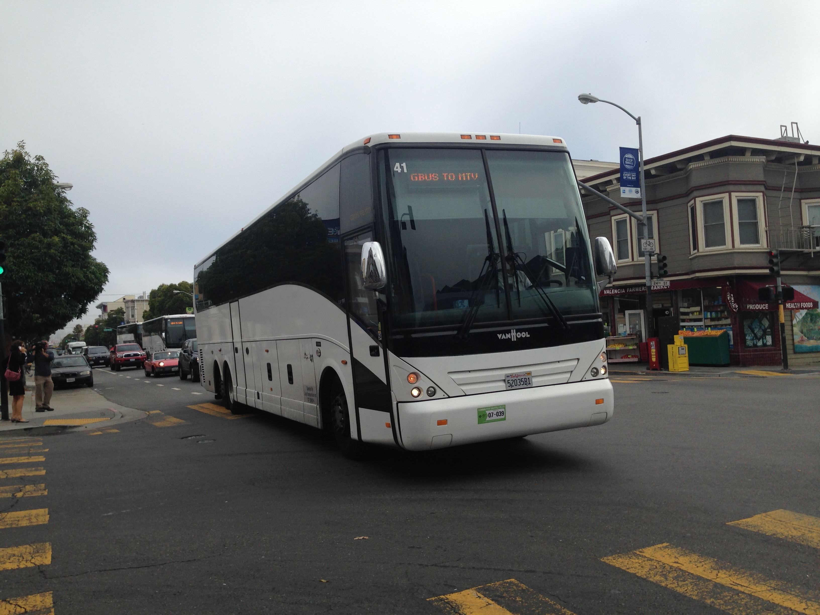 A commuter shuttle headed to Google's Mountain View campus pulls into a pre-approved Muni stop at 24th St and Valencia.
