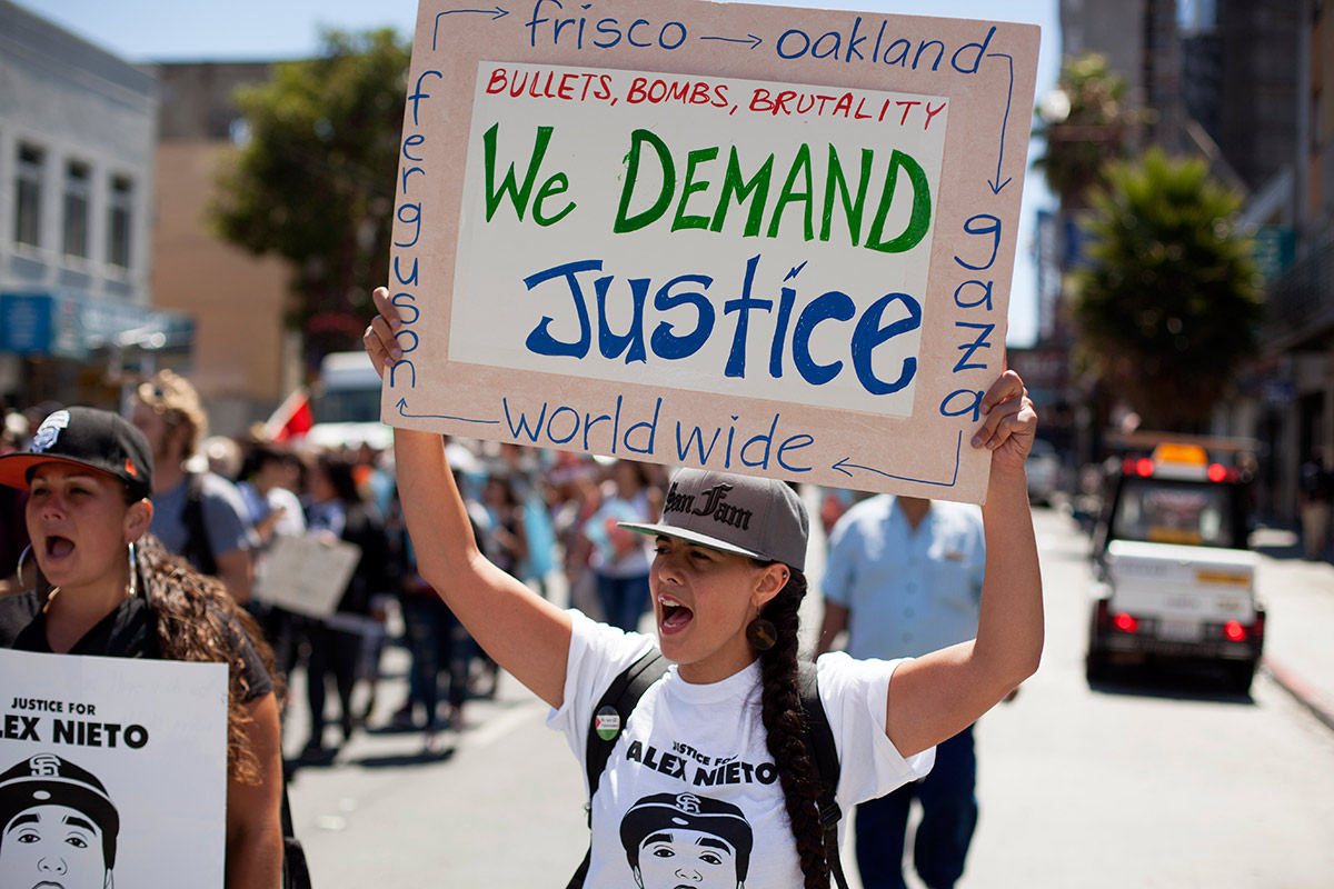 City College of San Francisco student Rima Miles marches down Mission Street on Friday protesting the fatal police shooting of Alejandro Nieto in March. (Mark Boyer/KQED)