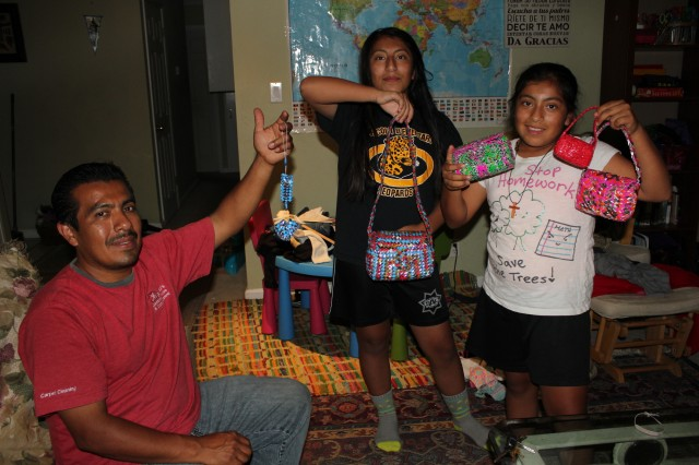 Gerardo Mendoza and daughters Esther (12) and Kelly (10) show items Mendoza made for them while being held in ICE detention for 26 months--purses and tiny shoes out of recycled Ramen noodle rappers. Mendoza's wife and three children didn't see him in person for more than two years. Though he was released a few months ago, he's still awaiting a final decision in his quest for US status.