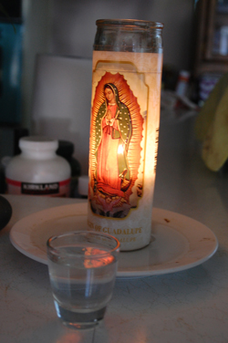 A candle burns bright at Yesenia's home. Cruz says her faith helped to bring her peace as she fled El Salvador. (Gabriel Salcedo/KQED)