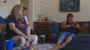 Nancy Holmes (left) and other residents spend time in the living room of the Dakota Eco Garden. (Adam Grossberg/KQED)