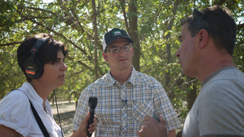 Sasha Khokha (left) and Scott Shafer (right) interview Dominic Pitigliano (center) at an almond orchard in Tulare County. (Suzie Racho/KQED)