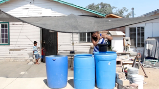 Gladys Colunga gathers water from buckets outside of her home in  Monson.(Jeremy Raff/KQED)