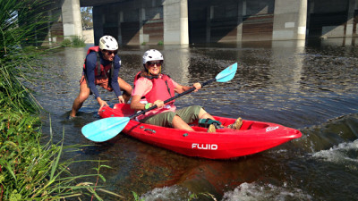 Sebastian Marlow, a guide with L.A. River Kayak Safari, helps a kayaker get into the water. (Avishay Artsy/KQED)