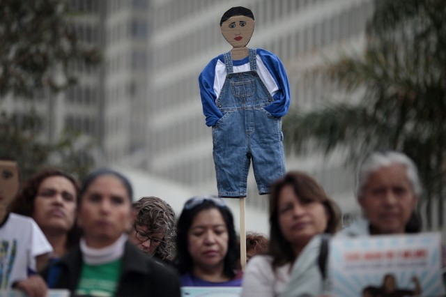 A protester holds up a cardboard cutout of a child before a march protesting deportation of minors and families. (James Tensuan/KQED)