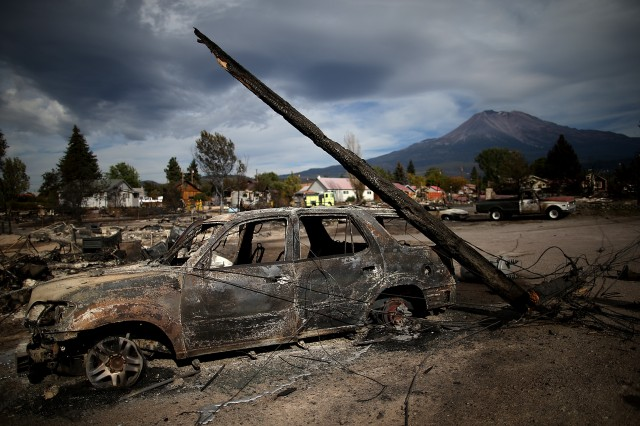 A burned utility pole rests on a burned-out car that sits among the remains of a destroyed home in Weed, California. (Justin Sullivan/Getty Images)