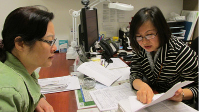 Health care worker Judy Leung (R) helps patient/client Ivy Hong select a health plan for her and her family at the Northeast Medical Services clinic on Stockton Street in San Francisco. (Scott Shafer/KQED)