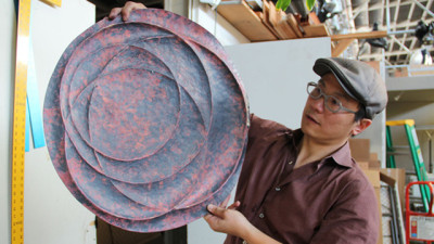Artist Nick Dong displays a copper wall hanging he's making at American Steel. (Erik Neumann/KQED)