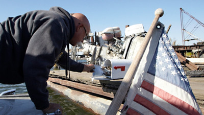 Rick Stelzreide leans over the side of his boat to deliver a Delta resident's mail. (Tony George/KQED)