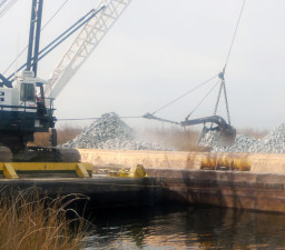 A crane barge takes a load off a rock barge as part of a levee maintenance operation in the Delta. (Lisa Morehouse/KQED)