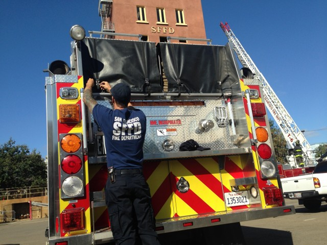 A member of the San Francisco Fire Department prepares an engine that's heading to the King Fire, northeast of Placerville. (Isabel Angell/KQED)