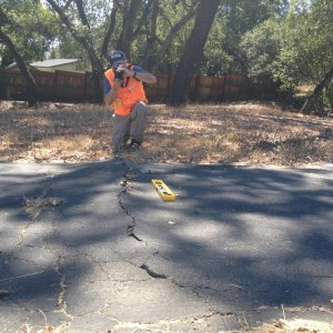 USGS geologist David Schwartz identifies which surface cracks in the west Napa Valley offer clues to the location of faults that caused the magnitude-6 South Napa Earthquake on August 24. Schwartz says this buckling of a driveway is from ground shaking, not a direct indicator of the fault's location. (Craig Miller/KQED)
