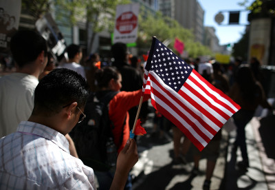 A marcher carries a U.S. flag on San Francisco's Market Street during 2013 immigration rally. (Justin Sullivan/Getty Images)