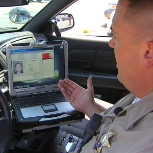 A Los Angeles County sheriff's deputy demonstrates a mobile fingerprint reader. Officials say biometric information would be retained indefinitely. (KNBC-TV)