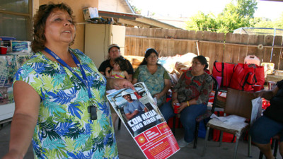 At a backyard meeting in Tulare, Sandra Garcia takes the opportunity to hand out pamphlets on workplace sexual harassment. (Grace Rubenstein/KQED)