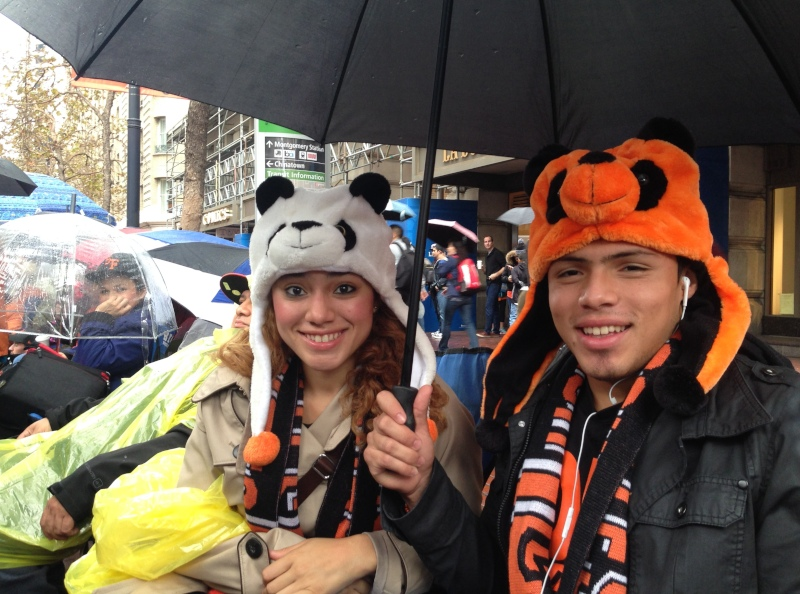 """Aileen Castillo of Sacramento, with her brother Alejandro, came down from Sacramento for the Giants victory celebration. """"We're ready for the rain -- we've got umbrellas, ponchos, raincoats-- we're fine."""" (Jeremy Raff/KQED)"""