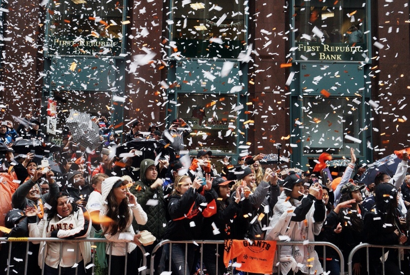 Confetti and rain pour down on fans along Market Street. (James Tensuan/KQED)
