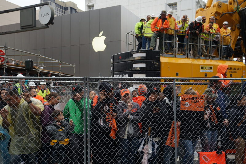 People tried to peer past the construction near Market St. (or climb on top of it) to better see the parade. (James Tensuan/KQED)
