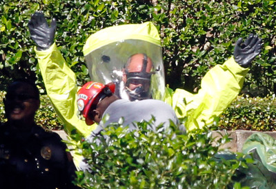 Hazmat workers help each other put on protective clothing before entering a Dallas apartment complex where a second health care worker who has tested positive for the Ebola virus resides. ( Mike Stone/Getty Images)