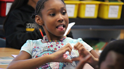 A Malcolm X fourth-grader makes a heart with her hands in class. (Sara Bernard/KQED)