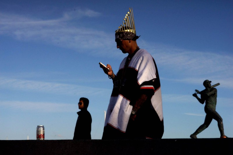 Peter Regaldo checks his phone outside of AT&T Park prior to Game Three of the World Series. (James Tensuan/KQED)