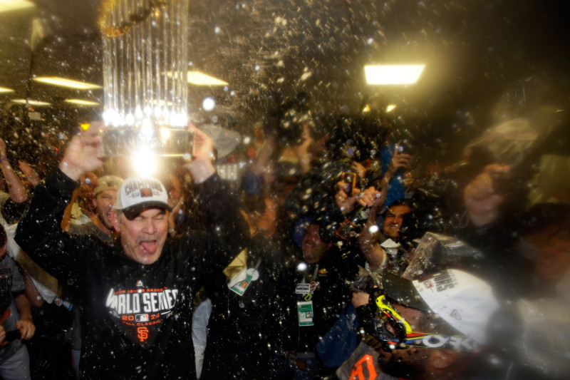 Bruce Bochy #15 of the San Francisco Giants celebrates with The Commissioner's Trophy in the locker room after a 3-2 win over the Kansas City Royals. (Ezra Shaw/Getty Images)