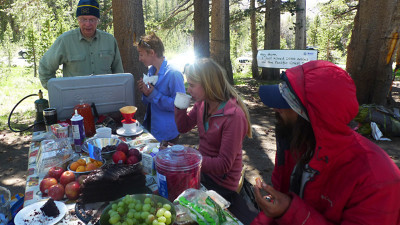 Hank Magnuski (L) feeds hikers, including some who took advantage of his wifi with their smartphones. (Lisa Morehouse/KQED)