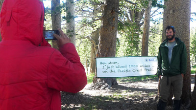 Magnuski brings a sign for hikers to take their photos next to, marking the first 1,000 miles of the PCT. (Lisa Morehouse/KQED)