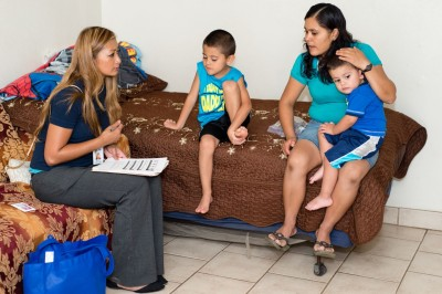 During a home visit Maura Vasquez, right, tells health educator Nunu Sixay that her son, Jovani, 6, has not been to the emergency room since learning that administering his medication more regularly could help alleviate his asthma. (Heidi de Marco/KHN).