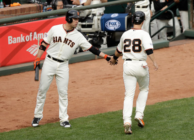 Buster Posey celebrates with Travis Ishikawa after Posey scores in the first inning against the St. Louis Cardinals during Game Three of the NLCS in San Francisco. (Photo by Ezra Shaw/Getty Images)