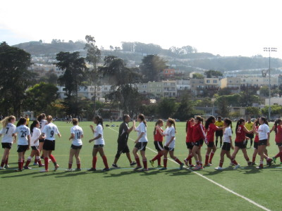 Members of the San Francisco Vikings U-16 girls club soccer team, Athena White, greet their opponents after winning a recent game. (David Weir/KQED)