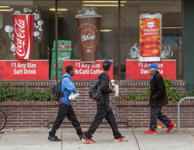 Two high-school students on their lunch break carry food and drink out of the McDonald's on University Avenue in Berkeley.  (Gael McKeon/Berkeleyside)