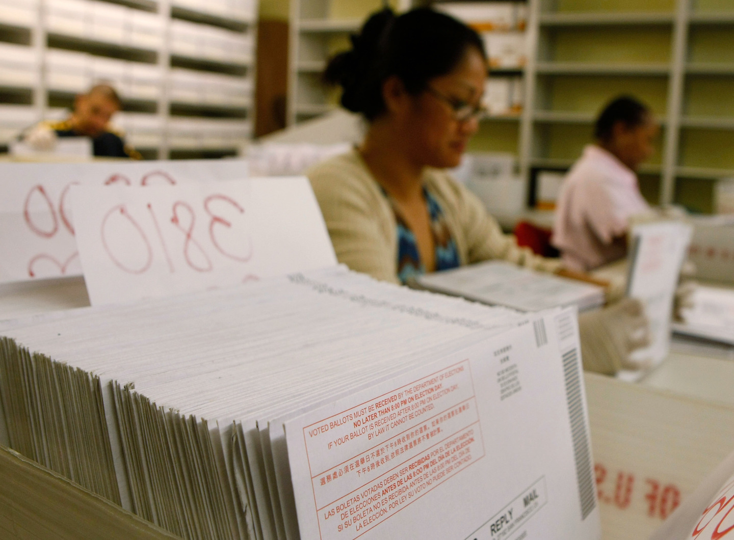 Workers at the San Francisco Department of Elections sort stacks of vote-by-mail ballots by precinct during a past election. (Justin Sullivan/Getty Images)
