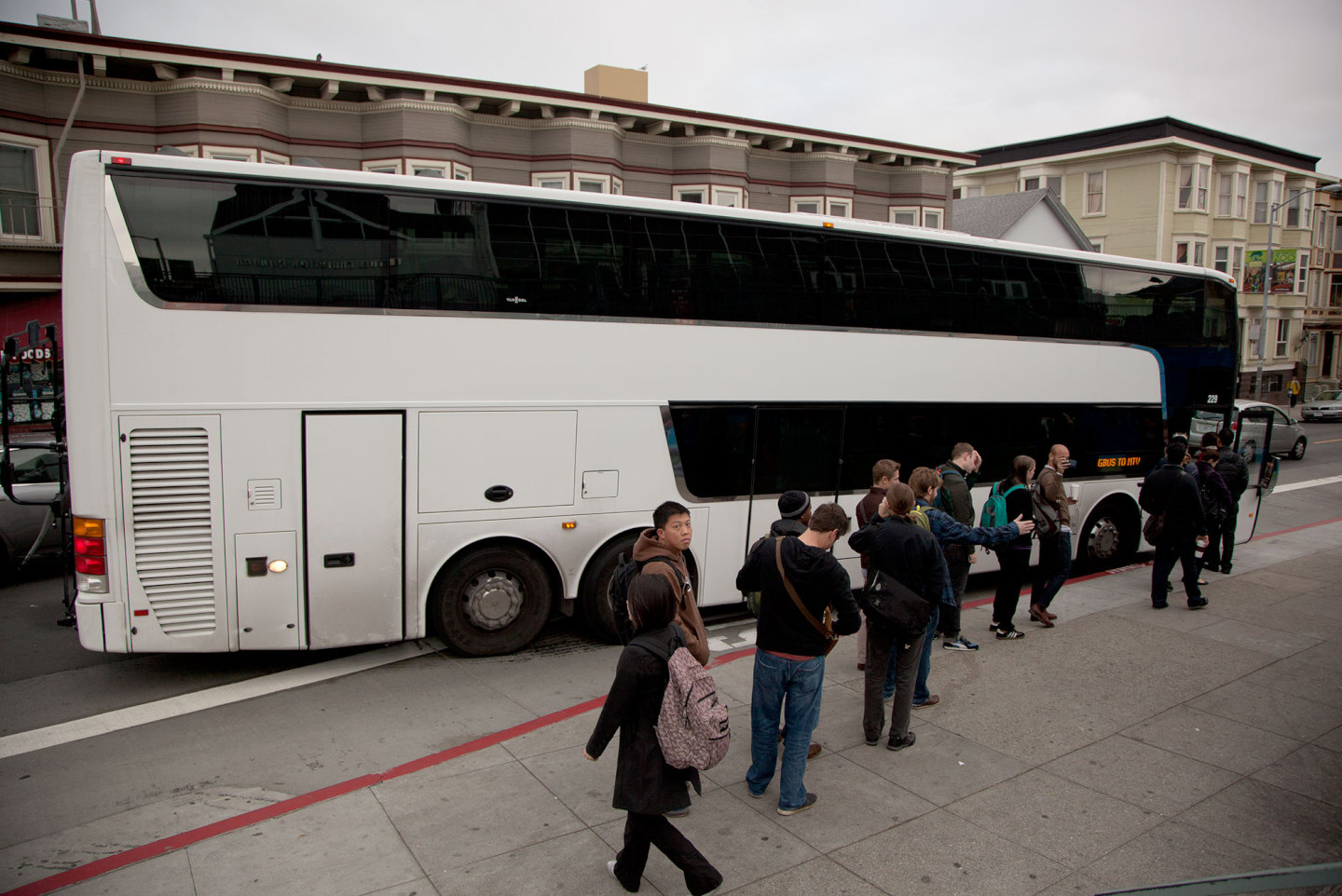 Workers board a private bus at a Muni bus stop at 24th and Valencia streets in the Mission District. (Mark Andrew Boyer/KQED)